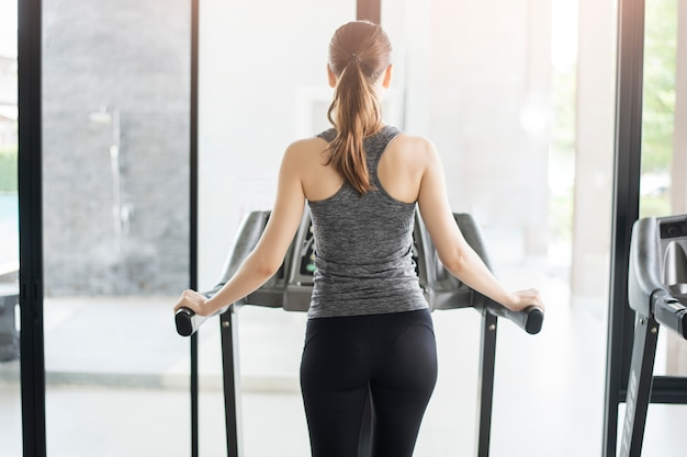Volver deporte mujer correr en la cinta en el gimnasio, estilo de vida saludable