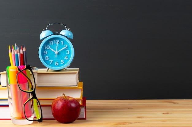 Volver a la escuela manzana y libros con lápices y anteojos sobre pizarra.