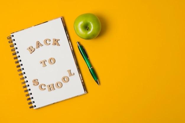 Volver a la libreta de la escuela con fondo naranja