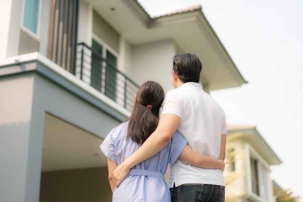 Volver retrato de joven pareja asiática de pie y abrazándose juntos mirando feliz frente a su nueva casa para comenzar una nueva vida.