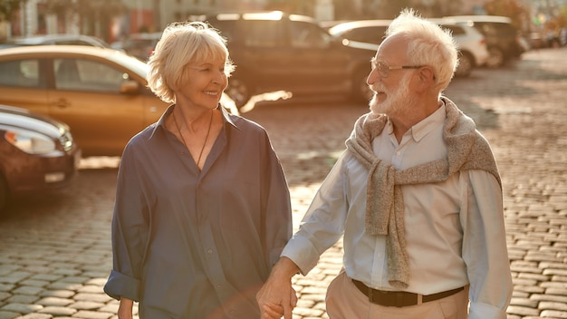 Volviendo a casa feliz pareja de ancianos tomados de la mano y mirando el uno al otro con una sonrisa mientras camina