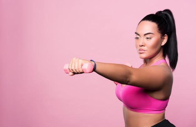Volviéndose mas fuerte. mujer mulata bastante gordita haciendo ejercicios de boxeo con pesas