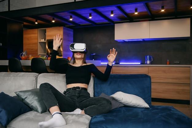 Vr emocionada chica milenaria con casco de realidad virtual jugando videojuego enfoque selectivo interior