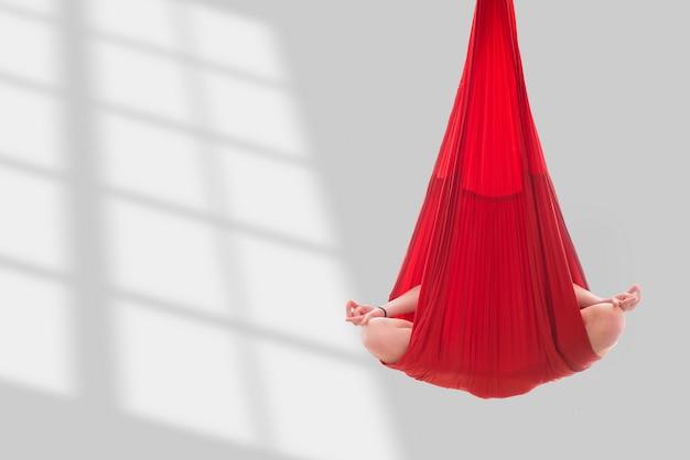 Vuela yoga. una niña sentada en una posición de loto en una hamaca roja
