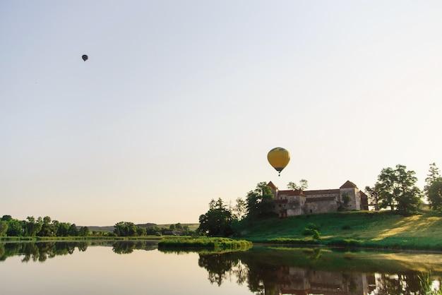 Vuelos en globo en la naturaleza. globos multicolores del aire caliente que vuelan sobre castillo cerca del lago al amanecer.