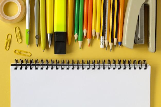 De vuelta a la escuela . abra el cuaderno de la maqueta vacía y la papelería escolar coloreada. fondo de papel amarillo.