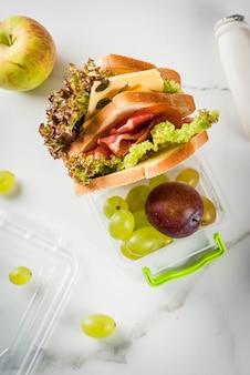 De vuelta a la escuela. un almuerzo saludable en una caja es fruta fresca, manzanas, ciruelas, uvas, una botella de yogurt y un sándwich con lechuga, tomate, queso y carne. mesa de mármol blanco. vista superior