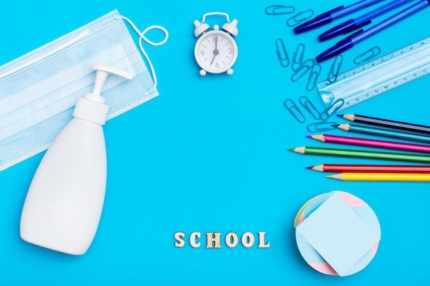 De vuelta a la escuela. distanciamiento social. papelería, mascarilla protectora y desinfectante sobre fondo azul.