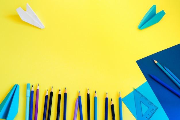 De vuelta a la escuela. espacio de trabajo creativo, moderno, minimalista, escolar o de oficina con suministros azules en amarillo