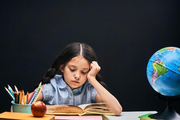 De vuelta a la escuela. estudiante guapo concentrado leyendo un libro sentado en la mesa.