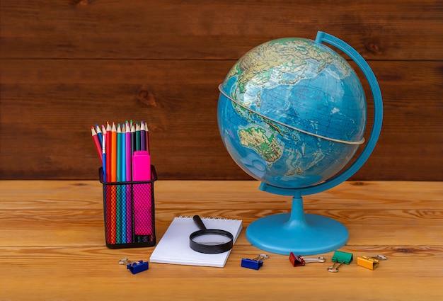 ¡de vuelta a la escuela! globo, modelo de la tierra, material educativo sobre una mesa de madera en un globo de asia y australia.