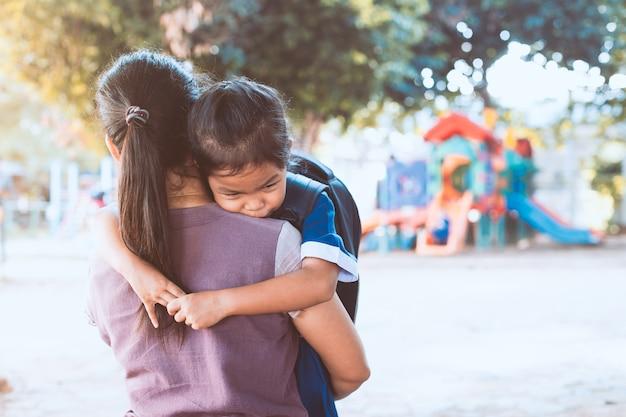 De vuelta a la escuela. linda chica asiática alumno con mochila abrazando a su madre con tristeza