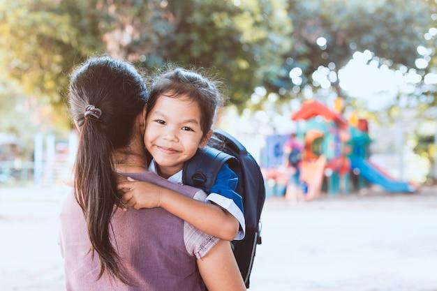De vuelta a la escuela. linda chica de pupila asiática con mochila abrazando a su madre en el patio de recreo