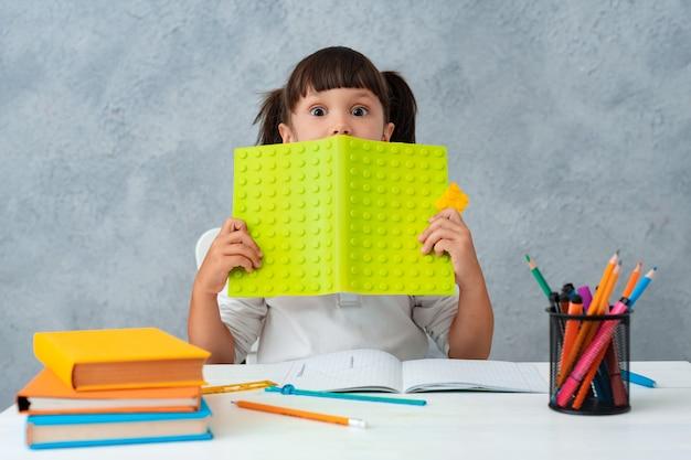 De vuelta a la escuela. linda colegiala niño sentado en un escritorio en una habitación.