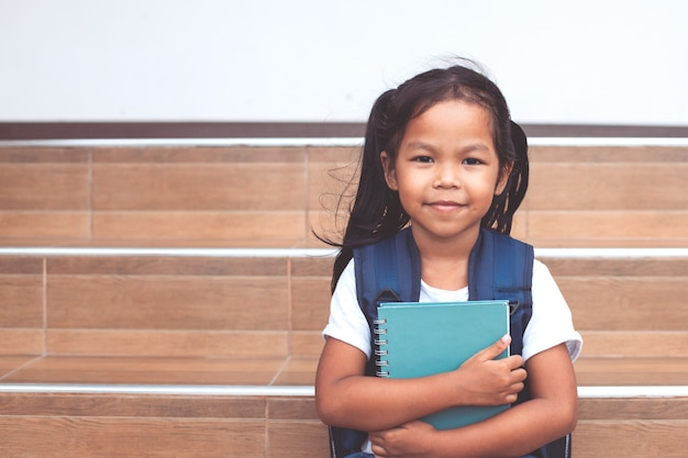 De vuelta a la escuela. linda niña asiática niño con mochila sosteniendo un libro en la escuela