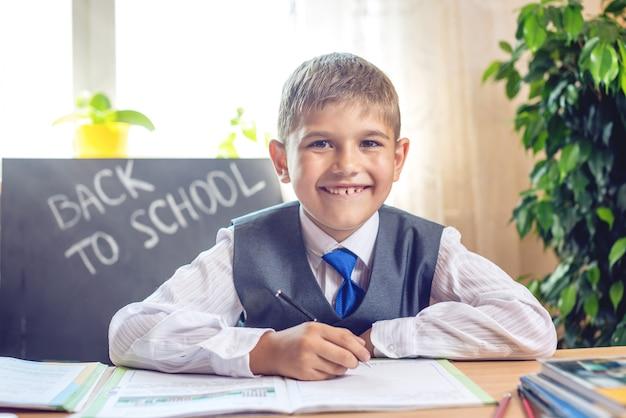 De vuelta a la escuela. lindo niño sentado en el escritorio en el aula.