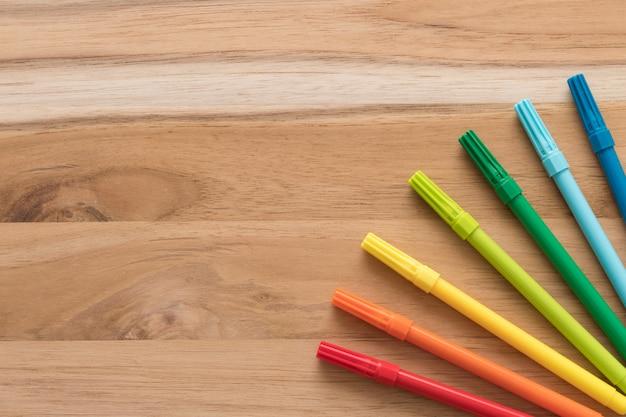 De vuelta a la escuela. marcador de punta de fieltro. pluma del cepillo de la acuarela en fondo de madera.