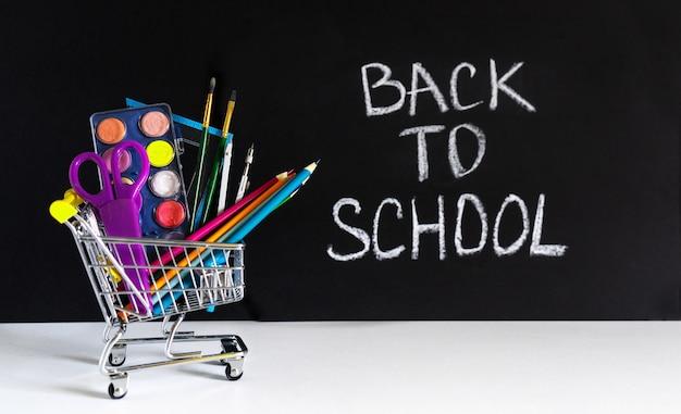 De vuelta a la escuela. mini carrito de compras con lápices y útiles escolares.