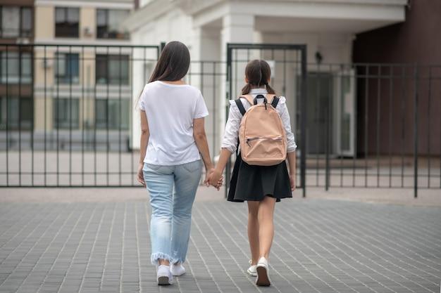 De vuelta a la escuela. mujer en jeans con colegiala en uniforme escolar caminando del brazo a la escuela