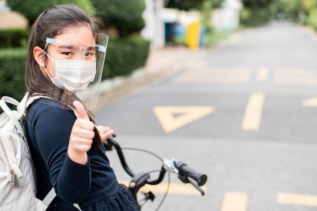 De vuelta a la escuela. niña asiática con mascarilla y dando pulgar arriba con mochila en bicicleta y yendo a la escuela. pandemia de coronavirus. nuevo estilo de vida normal. concepto de educación.