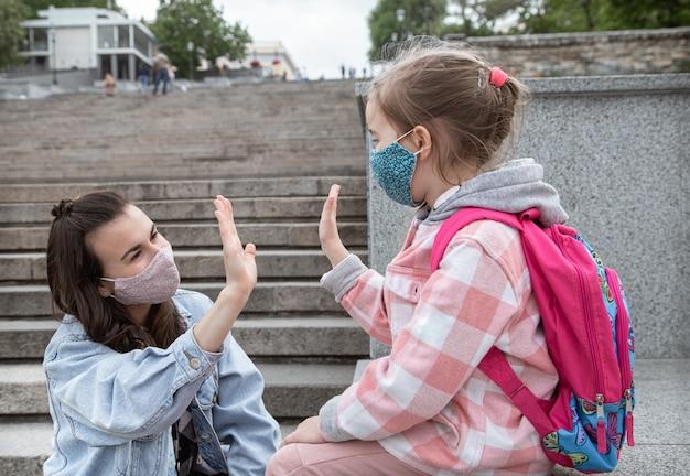 De vuelta a la escuela. los niños de la pandemia de coronavirus van a la escuela con máscaras. relaciones amistosas con la madre. educación infantil.