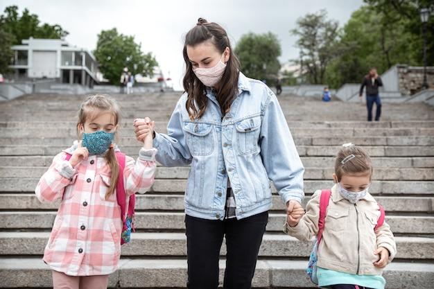 De vuelta a la escuela. los niños de la pandemia de coronavirus van a la escuela con máscaras. relaciones amistosas con mi madre.