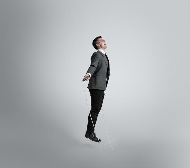 De vuelta en la niñez. se siente como pájaro libre. hombre en ropa de oficina entrenando con saltar la cuerda en la pared gris. aspecto inusual para hombre de negocios en movimiento, acción. deporte, estilo de vida saludable, trabajo.
