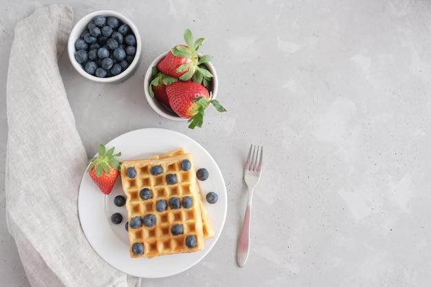 Wafdi belga o vienesa casera fresca con fresas orgánicas frescas de fresas y arándanos