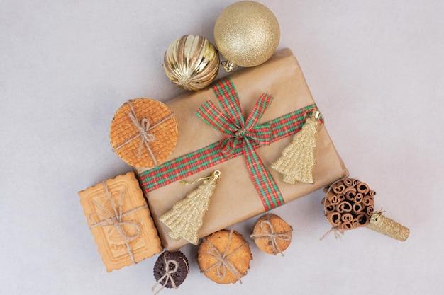 Waffle en cuerda con regalo y bolas de navidad doradas sobre mesa blanca.