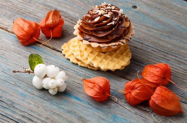 Waffle dulce, pastel con crema y physalis sobre un fondo de madera