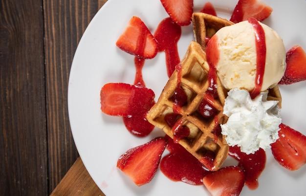 Waffle con fresas, helado de vainilla y crema batida