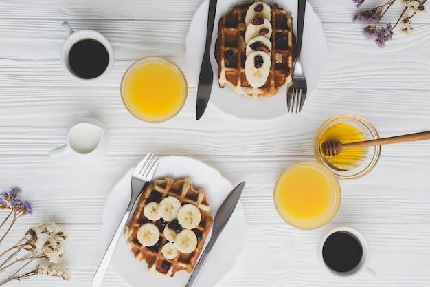 Waffle con plátanos cerca de las bebidas