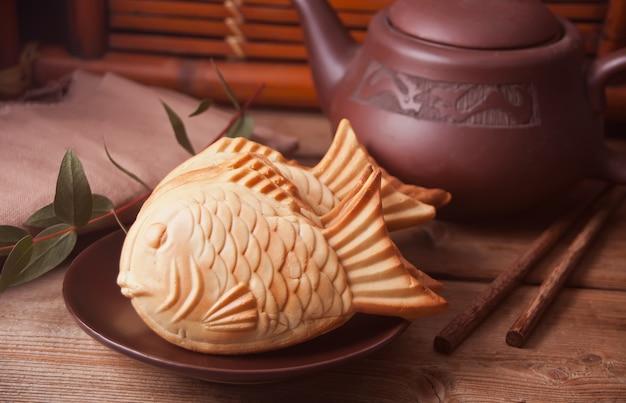 Waffle de relleno dulce en forma de pescado de la comida de calle de taiyaki en la tabla de madera