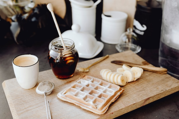 Waffle y rodajas de banana en una bandeja de madera junto a un tarro de miel