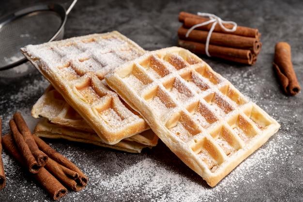 Waffles apilados con azúcar en polvo y palitos de canela