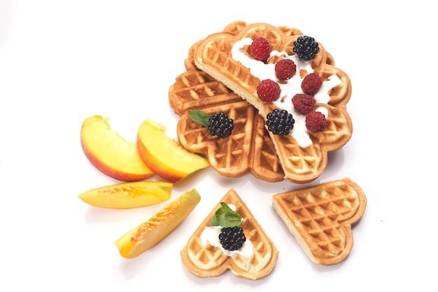 Waffles con bayas y melocotones aislados