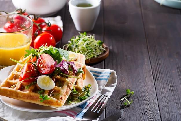 Waffles belgas con aguacate, huevos, microverde y tomates con jugo de naranja en mesa de madera