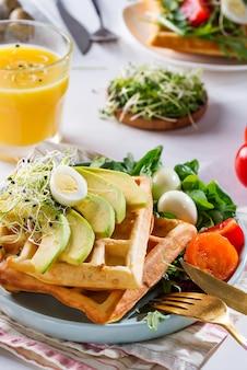 Waffles belgas con aguacate, huevos, microverde y tomates con jugo de naranja sobre mesa de mármol