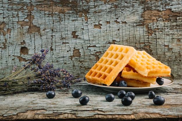 Waffles belgas con bayas cerca del ramo