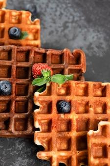 Waffles belgas de chocolate y vainilla con bayas frescas en un plato de cerámica