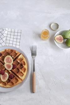 Waffles belgas higos frambuesas miel café exprés fondo blanco de madera endecha plana