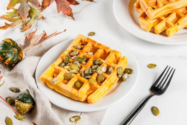 Waffles de calabaza caseros con jarabe de arce y semillas de calabaza, en mesa de mármol blanco, espacio de copia
