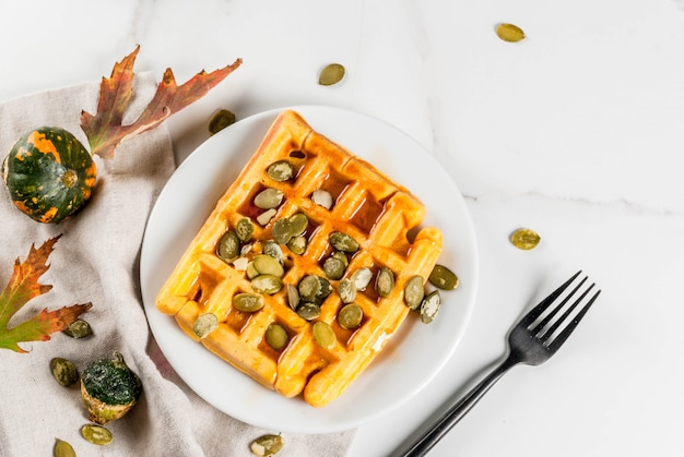 Waffles de calabaza caseros con jarabe de arce y semillas de calabaza, sobre mesa de mármol blanco