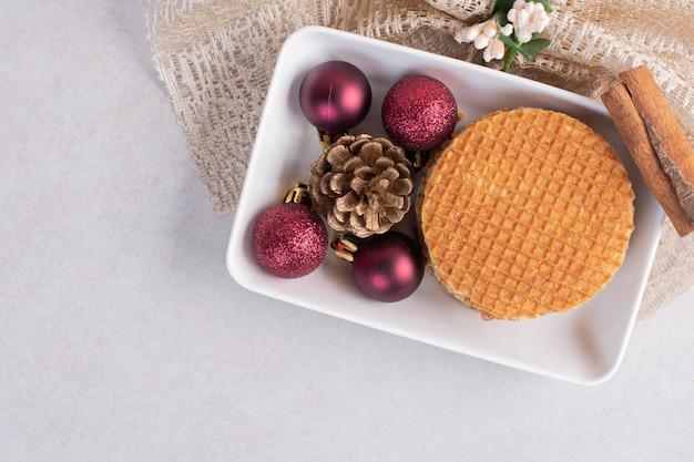 Waffles con canela y juguetes de navidad en plato blanco.