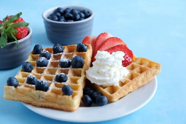 Waffles caseros vieneses frescos con bio fresas y arándanos y crema batida sobre un fondo azul.