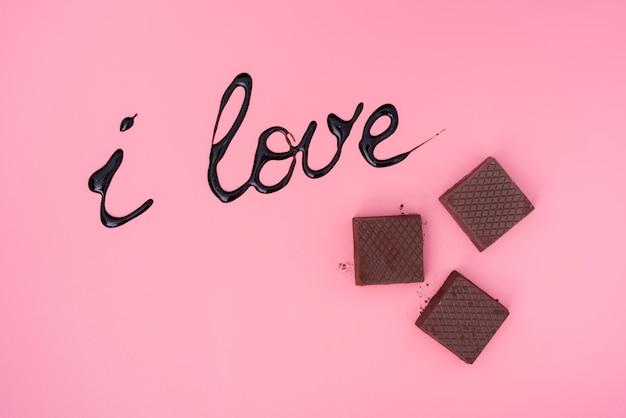 Waffles de chocolate sobre fondo rosa con jarabe de chocolate escrito
