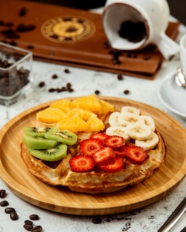Waffles cubiertos con frutas mixtas en rodajas