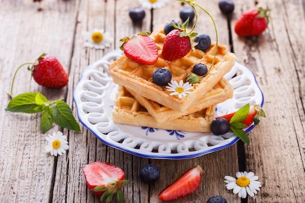Waffles con fresas y arándanos para el desayuno, belga.