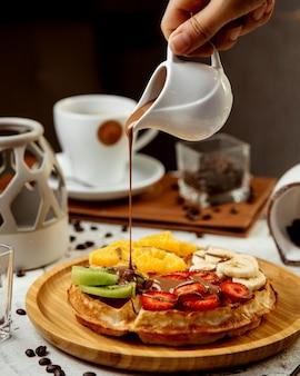 Waffles con frutas en rodajas y chocolate caliente