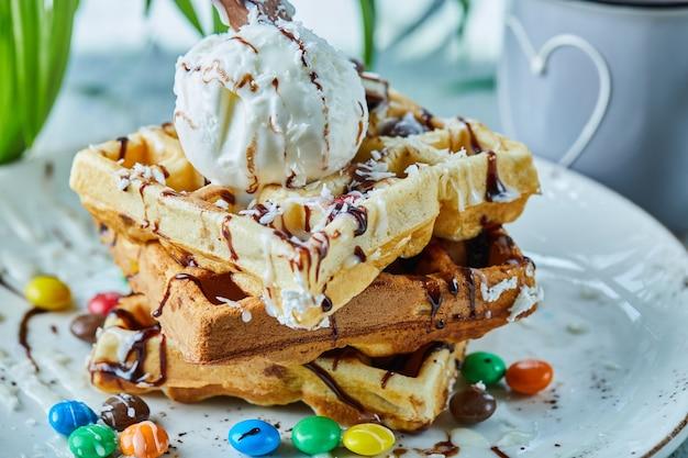 Waffles con helado, chocolate, bolas de chocolate en el plato blanco con té